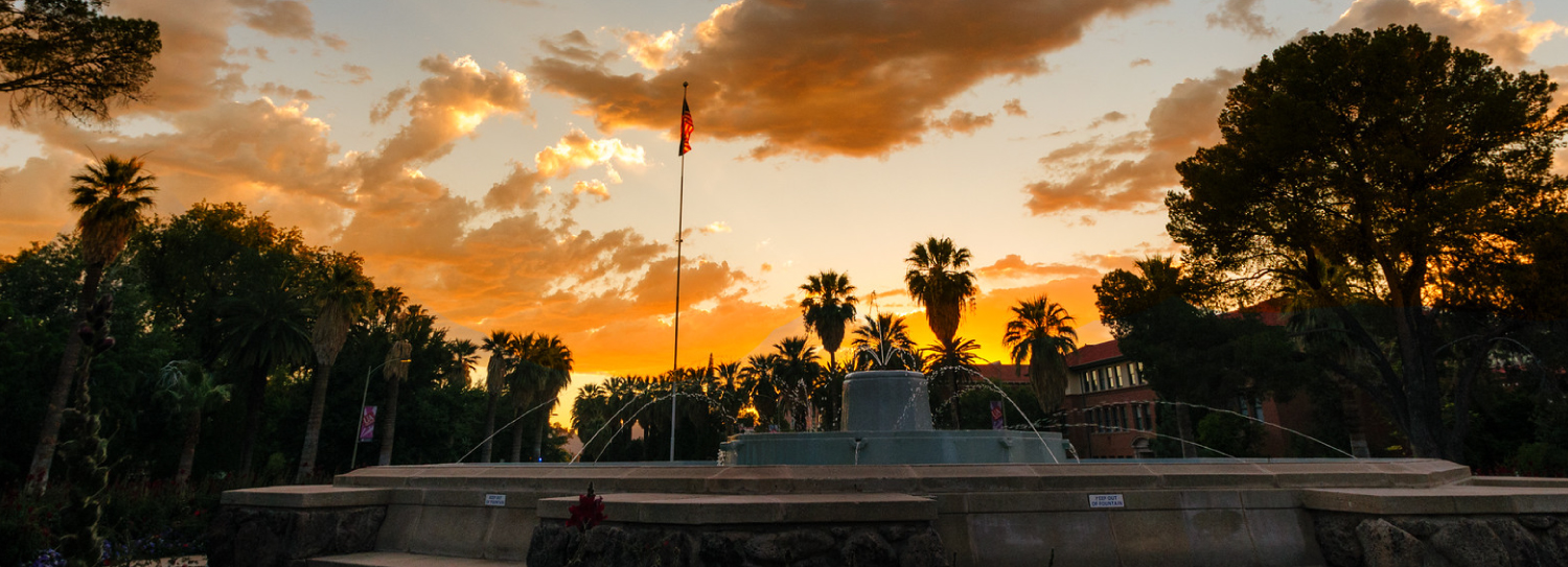 Old Main Fountain is seen as the sun is setting on campus